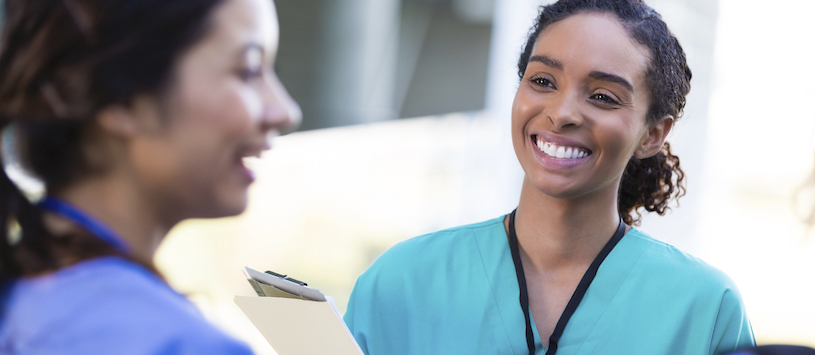 Medical employee smiling at a coworker.