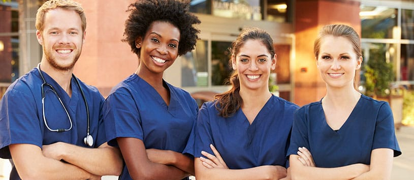 Four Practical Nursing students standing together.